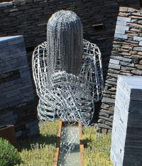 Sculpture of young woman hanging her head down made from chains
